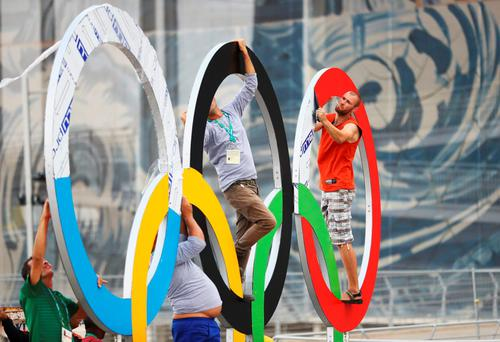 Workers install a set of Olympic Rings at the Olympic Park. Photo: Ryan Pierse/Getty Images