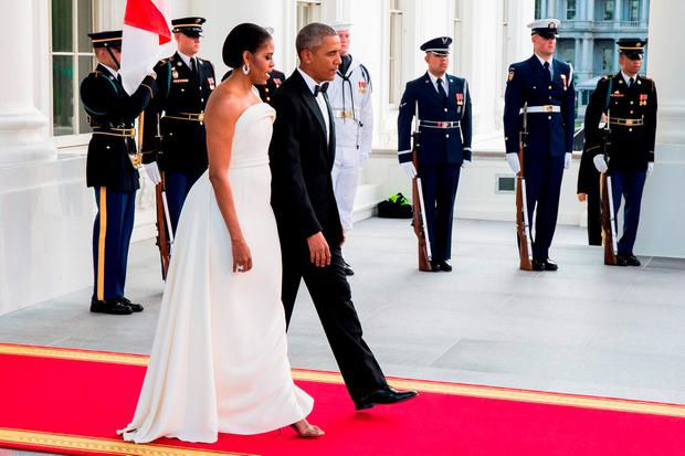 US President Barack Obama and First Lady Michelle Obama make their way onto the North Portico before the arrival of Singapore Prime Minister Lee Hsien Loong and his wife, Ho Ching at The White House before a state dinner