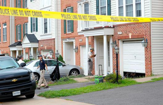 Law enforcement officers are seen outside the home of Nicholas Young, a Washington Metro Transit Officer, Wednesday (AP Photo/Pablo Martinez Monsivais)