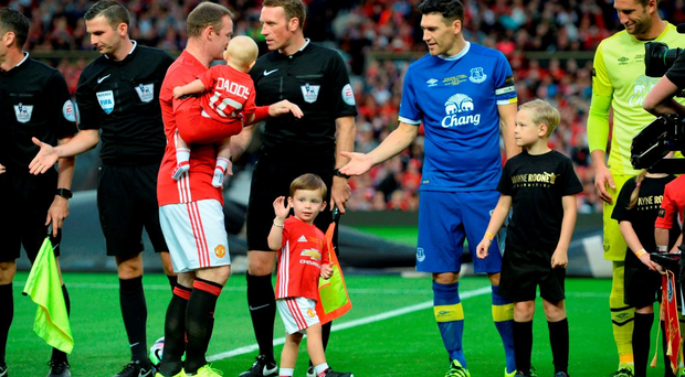 Manchester United's English striker Wayne Rooney (CL) shakes hands with the opposition players with his sons Klay and Kit before his testimonial. Getty Images