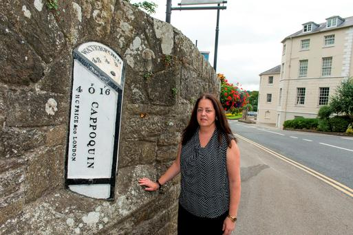 Mealla Fahey of Lismore Heritage shows an old milestone in Lismore, one of which has been stolen. Photo: Michael Mac Sweeney
