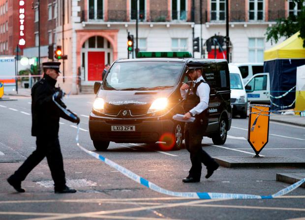 A body is driven away in a private ambulance from the scene in Russell Square, central London, after a knife attack in which a woman in her 60s was killed and five people were injured