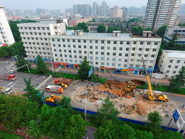 Aerial view of rescuers working at giant hole resulted from road collapse on August 2, 2016 in Zhengzhou, Henan Province of China