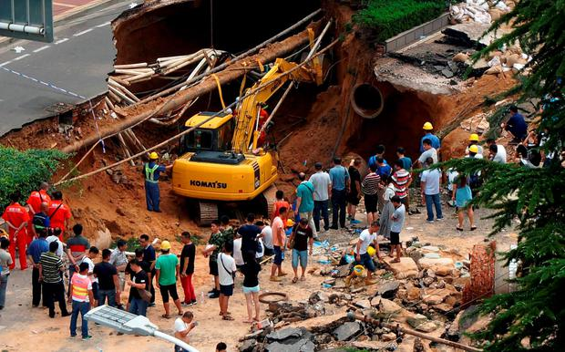 This photo taken on August 2, 2016 shows rescuers searching for missing people after a giant sinkhole opened up on a road in Zhengzhou, in central China's Henan province