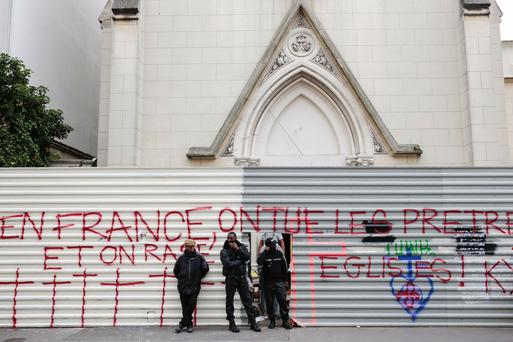 Members of a private security agency stand in front of a barrier with an inscription which translates as