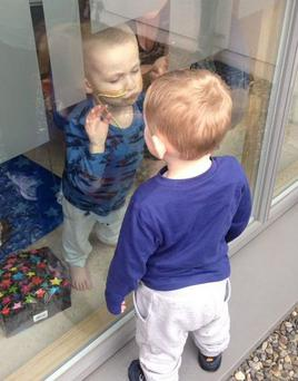 Ryan Coyle (2) meets his cousin Nathan (2) through the glass following a bone marrow transplant Credit: A Smile for Ryan