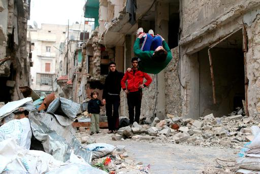 Gymnast Ahmad al-Sawas performs moves in the rebel-held Bustan al-Qasr neighbourhood of Aleppo. Photo: Reuters
