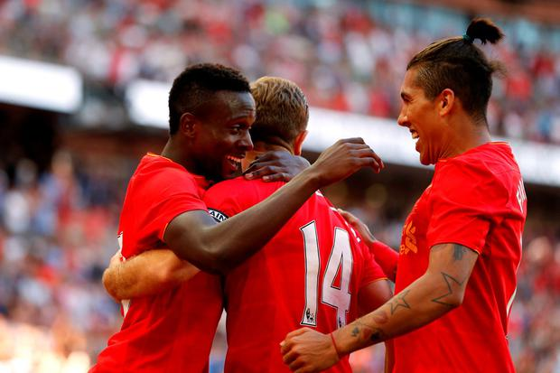 Liverpool's Divock Origi celebrates scoring their third goal with Roberto Firmino and teammates