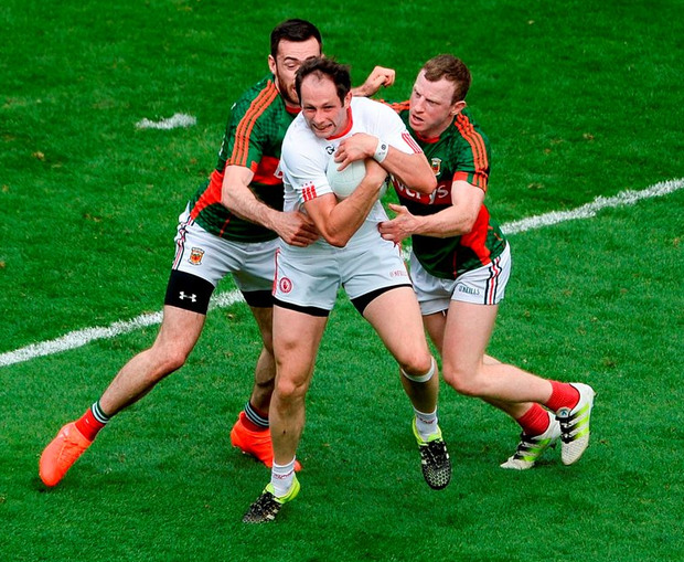 Ronan McNabb of Tyrone in action against Kevin McLoughlin and Colm Boyle of Mayo. Photo: Daire Brennan/Sportsfile