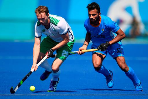 Ireland's Michael Darling and India's Chandanda Thimmaiah fight for the ball during the men's field hockey India v Ireland match. AFP/Getty Images