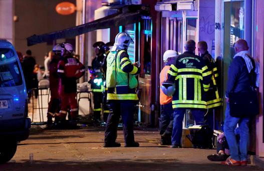 French firemen and rescue crew gather after a fire swept through a bar overnight, killing 13 people and injuring six, after a birthday cake with candles and sparklers fell to the floor and set the carpet ablaze. Photo: Boris Maslard/Reuters