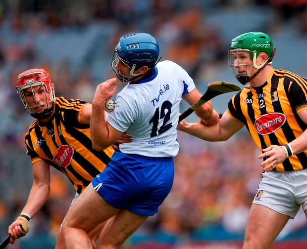 Michael Walsh is tackled by Kilkenny's Cillian Buckley (L) and Paul Murphy. Photo by Ray McManus/Sportsfile