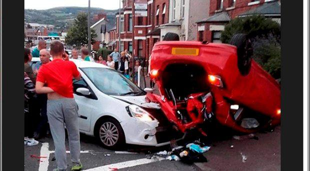 Driver ploughs into two parked cars before flipping over