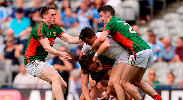 Sean Cavanagh – lying on the bottom of the ground – got a yellow card after this incident, in which Tyrone boss Mickey Harte claims he was provoked. Photo by Piaras Ó Mídheach/Sportsfile