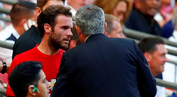 Manchester United boss Jose Mourinho speaks with Juan Mata after he is substituted during Sunday's Community Shield. Photo: Eddie Keogh / Reuters