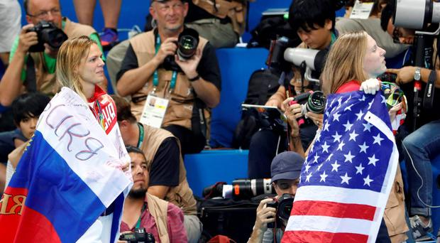USA's Lilly King (R), wrapped in her national flag poses next to silver medallist Russia's Yulia Efimova after she won the Women's 100m Breaststroke Final during the swimming event at the Rio 2016 Olympic Games at the Olympic Aquatics Stadium in Rio de Janeiro