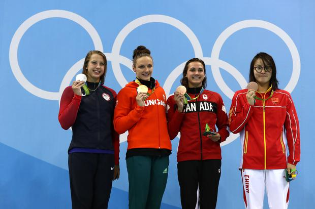Silver medalist Kathleen Baker of the United States, with gold medal medallist Katinka Hosszu of Hungary and bronze medalist's Kylie Masse of Canada and Yuanhui Fu of China pose on the podium