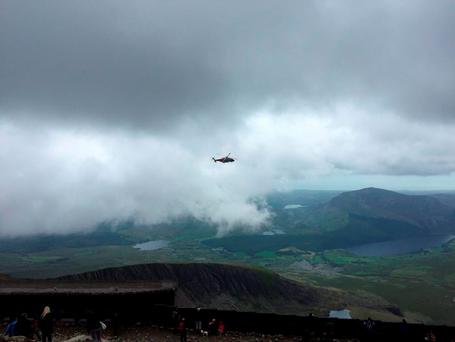 Handout photo taken with permission from the Twitter feed of @huw_price of a rescue helicopter in the Yr Aran area of Snowdonia, as North Wales Police said that emergency services are at the scene of an incident involving a helicopter
