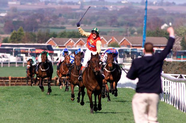 Paul Carberry waves his whip in celebration as Bobbyjo passes the winning post in the 1999 Aintree Grand National Picture: Owen Humphreys