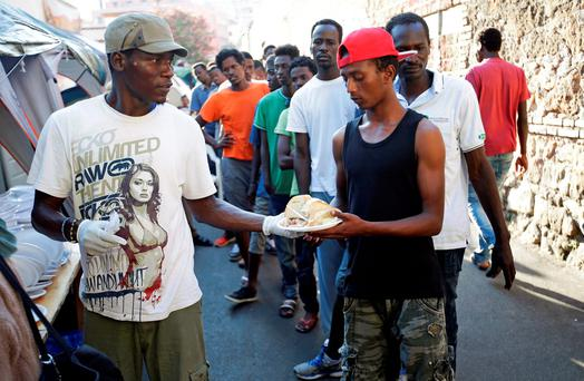 Migrants receive food from volunteers at a makeshift camp in Via Cupa in Rome, Italy. Photo: Max Rossi/Reuters