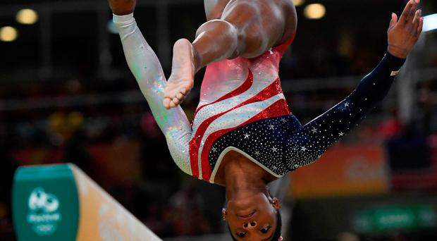 US gymnast Simone Biles competes in the Beam event during the women's team final Artistic Gymnastics at the Olympic Arena during the Rio 2016 Olympic Games in Rio de Janeiro on August 9, 2016. / AFP PHOTO / Ben STANSALLBEN STANSALL/AFP/Getty Images