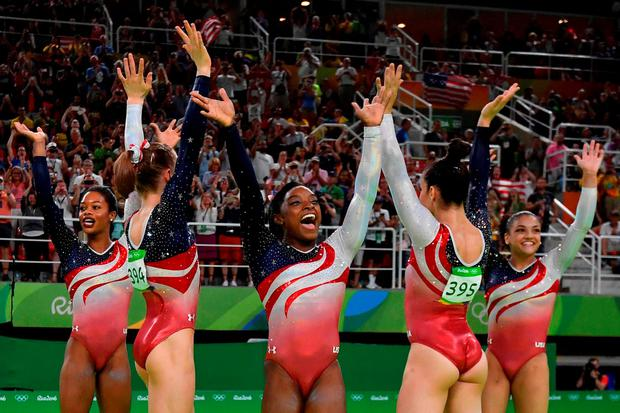 US gymnast Simone Biles (C) and her teammates celebrate after winning the women's team final Artistic Gymnastics at the Olympic Arena during the Rio 2016 Olympic Games