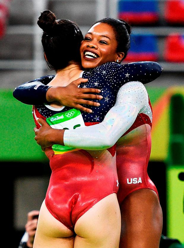 Alexandra Raisman (L) and Gabrielle Douglas (R) of the United States celebrate winning the gold medal during the Artistic Gymnastics Women's Team Final on Day 4 of the Rio 2016 Olympic Games