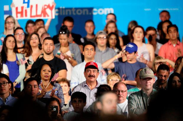 A man identified as Seddique Mateen (C-red ball cap), whose son shot and killed 49 people and injured 53 others inside the Pulse nightclub in June, sits with supporters at a rally for Democratic Presidential nominee Hillary Clinton at the Osceola Heritage Park in Kissimmee, Florida on August 8, 2016