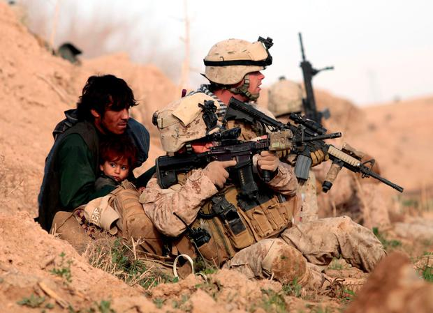 US-led Nato troops protect an Afghan man and his child after Taliban fighters opened fire. The same Nato alliance is also protecting Ireland – while we contribute nothing in return Photo: Goran Tomasevic/Reuters