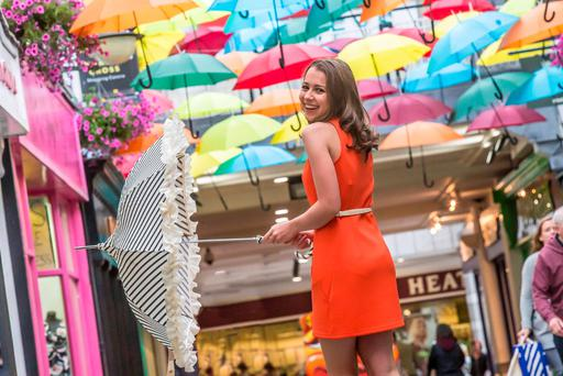 Kilkenny girl Eva Phelan was protected from the rain in the Market Cross Shopping Centre yesterday as artist Michael Browne has a colourful display of umbrellas hanging throughout the centre. The display has been getting a great reaction during the Kilkenny Arts Festival. Many suggestions have been made that the display should be left up all year round. Photo: Pat Moore