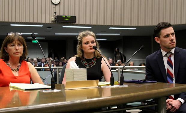 Angela, left and Aoife Beary, center, listen with Vice Consul Kevin Byrne of the Irish Consulate General, right, as state lawmakers in the Assembly Appropriations Committee discuss SB465 in Sacramento, Calif. (AP Photo/Darcy Costello)