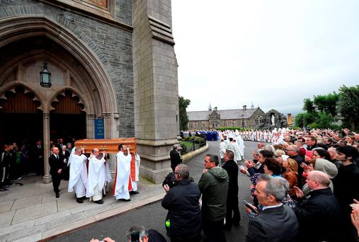 Hundreds of mourners applaud as the remains of the late retired Bishop of Derry, Dr Edward Daly, are carried from St Eugene's Cathedral. Photo: Getty