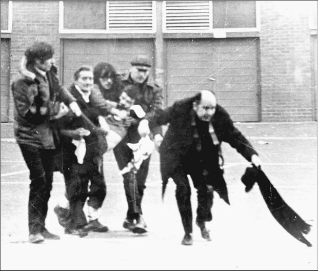 The crouched figure of the late former Bishop of Derry Edward Daly carrying a bloodstained handkerchief as the body of Jackie Duddy is carried away on Bloody Sunday