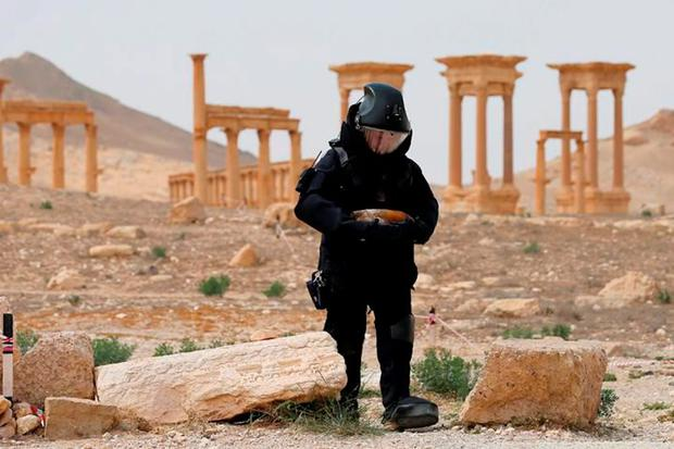 A Russian sapper works to clear mines in the historic part of Palmyra, Syria, earlier this year, after it was retaken from Isil. The jihadists carried out a mass killing in the ancient city before Syrian troops expelled them from it. Photo: Reuters