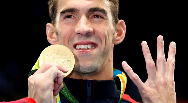 Gold medalist Michael Phelps of the United States celebrates during the medal ceremony for the Men's 200m Individual Medley Final on Day 6 of the Rio 2016 Olympic Games. Photo by Clive Rose/Getty Images