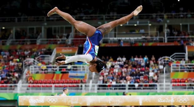 Simone Biles (USA) of USA competes on the beam during the women's individual all-around final. REUTERS/Damir Sagolj
