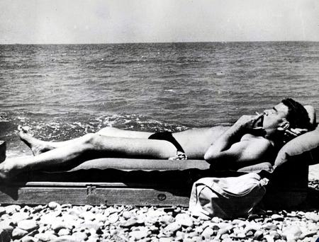 The spy who loved: Guy Burgess (pictured sunbathing on the beach of the Black Sea) faithfully served Stalin's regime while claiming to hate Russia