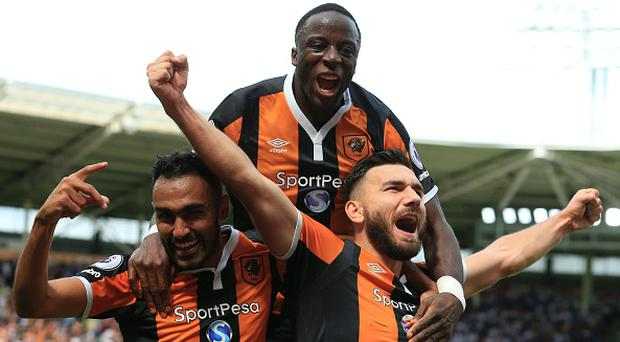 Hull City's Scottish midfielder Robert Snodgrass (R) celebrates with Hull City's Egyptian midfielder Ahmed Elmohamady (L) and Hull City's Norwegian striker Adama Diomande (C) after scoring their second goal during the English Premier League football match between Hull City and Leicester City at the KCOM Stadium in Kingston upon Hull, north east England on August 13, 2016. / AFP / Lindsey PARNABY / RESTRICTED TO EDITORIAL USE. No use with unauthorized audio, video, data, fixture lists, club/league logos or 'live' services. Online in-match use limited to 75 images, no video emulation. No use in betting, games or single club/league/player publications. / (Photo credit should read LINDSEY PARNABY/AFP/Getty Images)