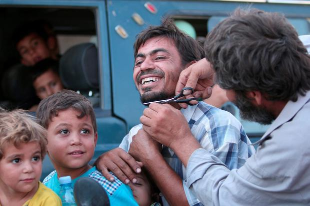 A man cuts the beard of a civilian who was evacuated with others by the Syria Democratic Forces (SDF) fighters from an Islamic State-controlled neighbourhood of Manbij, in Aleppo Governorate, Syria. REUTERS/Rodi Said