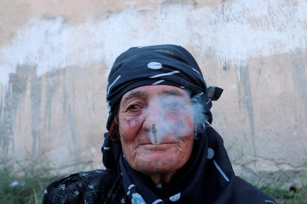 A woman smokes as she rests after she was evacuated with others from an Islamic State-controlled neighbourhood of Manbij, in Aleppo Governorate, Syria. REUTERS/Rodi Said