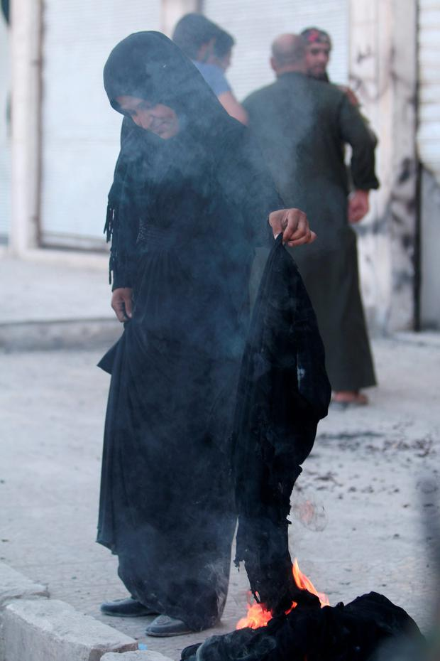A woman sets fire to a niqab after she was evacuated with others from an Islamic State-controlled neighbourhood of Manbij, in Aleppo Governorate, Syria. REUTERS/Rodi Said