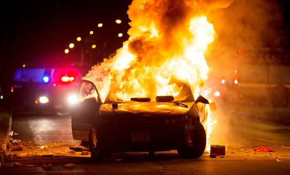 A car burns as a crowd of more than 100 people gathers following the fatal shooting of a man in Milwaukee, Saturday, Aug. 13, 2016
