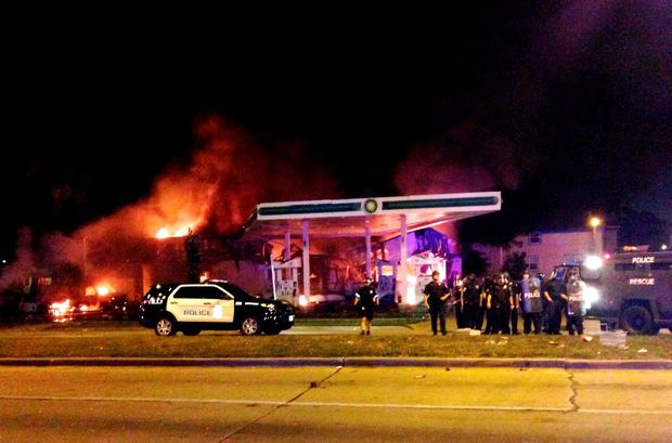 Authorities respond near a burning gas station as dozens of people protest following the fatal shooting of a man in Milwaukee, Saturday, Aug. 13, 2016