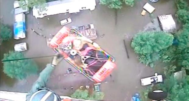 An aircrew from Coast Guard Air Station New Orleans rescues three people from a rooftop due to flooding in Baton Rouge, Louisiana, U.S., A in this still image from video taken on August 13, 2016. Coast Guard Air Station New Orleans/Handout via REUTERS
