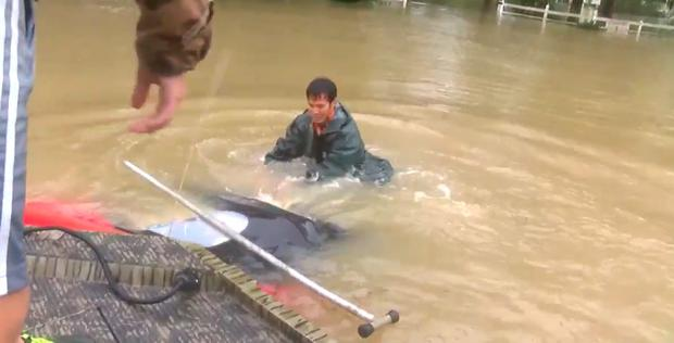 A rescuer pulls the woman from the sinking car