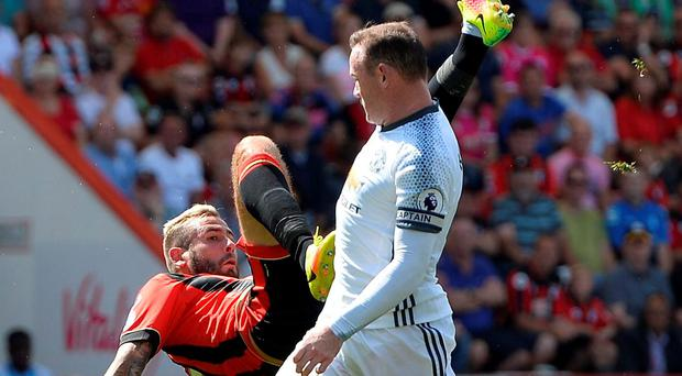 Bournemouth's Steve Cook falls to the ground under pressure from Manchester United's Wayne Rooney. Photo: Hannah McKay/Reuters