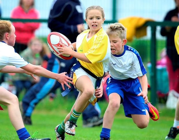 Amalita O Donoghue from Carlow tries to evade the tackle of Jack Hayes and Jody Schiller from Sligo during the under-11 tag rugby at the Community Games in AIT Athlone. Photo: Frank McGrath