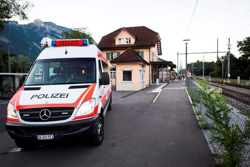 A police car stands at the train station following an attack on a train in Salez, Switzerland. A 34-year-old woman died from wounds suffered after a man attacked her and four others Picture: Gian Ehrenzeller/Keystone via AP