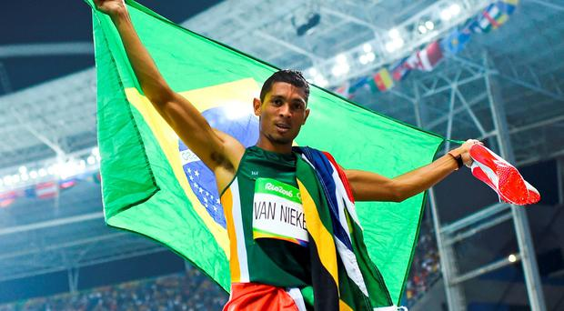 Wayde van Niekerk of South Africa celebrates with Brazilian flag