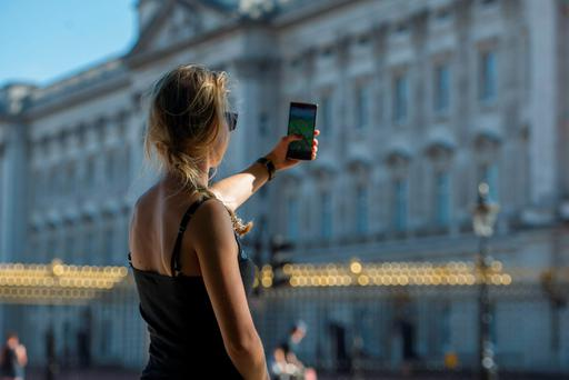 A tourist keeps a look-out for Pokemon outside Buckingham Palace in London. Photo: David Mirzoeff/PA Wire